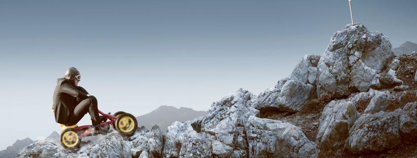 Geschftsmann mit Tretauto auf dem Weg zum Gipfel (© lassedesignen | fotolia.de)